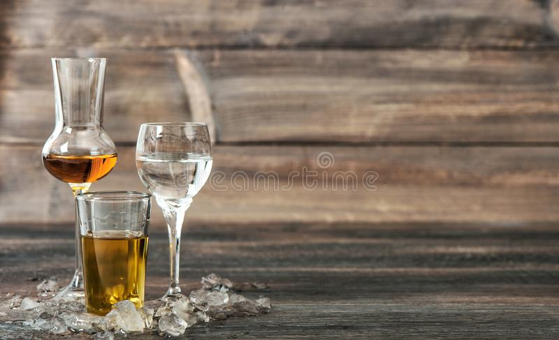 Alcoholic drinks with ice whisky liquor vodka. Alcoholic drinks with ice on wooden background. Whisky, liquor, vodka stock image
