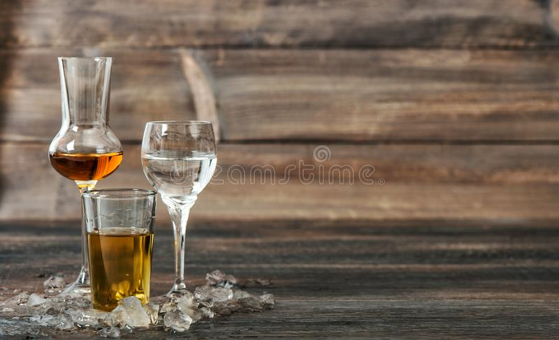 Alcoholic drinks with ice Aperitif whisky liquor vodka. Alcoholic drinks with ice on wooden background. Aperitif, whisky, liquor, vodka royalty free stock photos