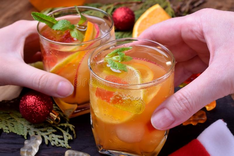 Alcoholic fizzy cocktail with white wine and fruit. Two glasses clink royalty free stock image