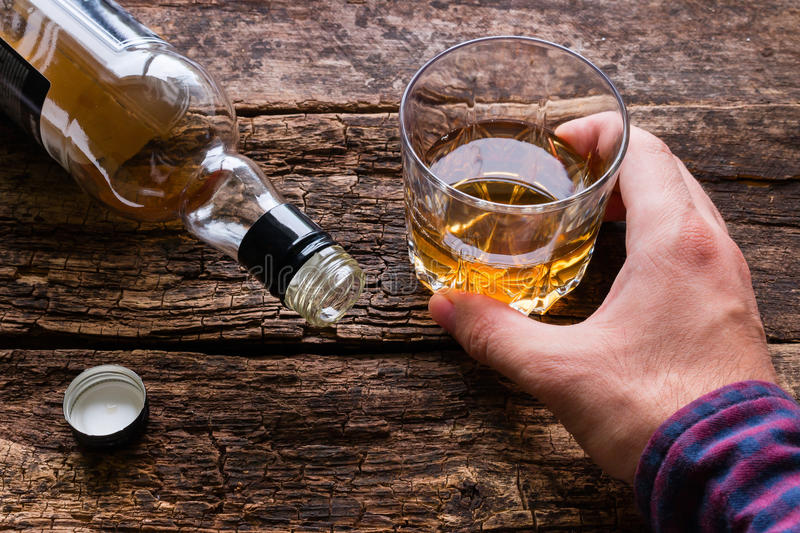 Alcoholic holding a glass of alcohol stock images
