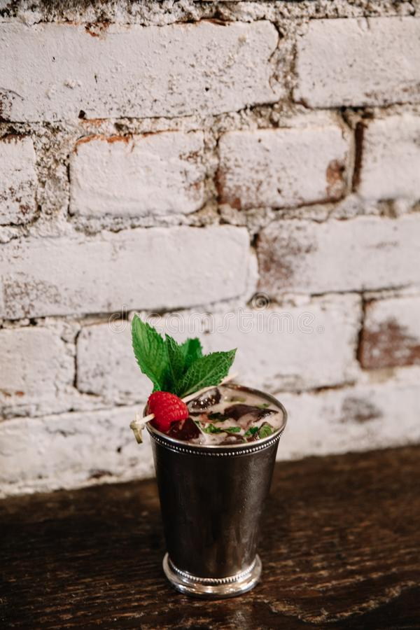 A mint julep cocktail against white background garnished with raspberries stock images