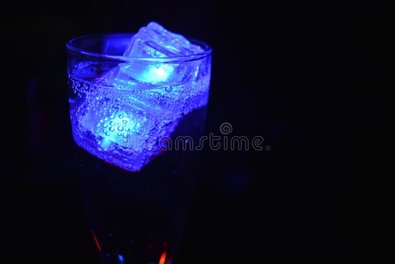 Stunning images of drinks with glowing ice cubes.  Bright colors with bubbles in a glass of champagne. Alcoholic and non-carbonated drinks in champagne bottles royalty free stock images