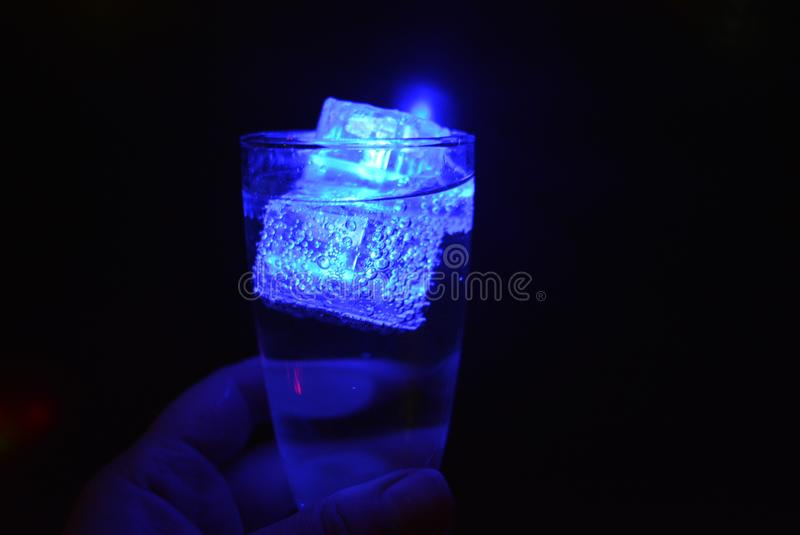 Stunning images of drinks with glowing ice cubes.  Bright colors with bubbles in a glass of champagne. Alcoholic and non-carbonated drinks in champagne bottles royalty free stock photos