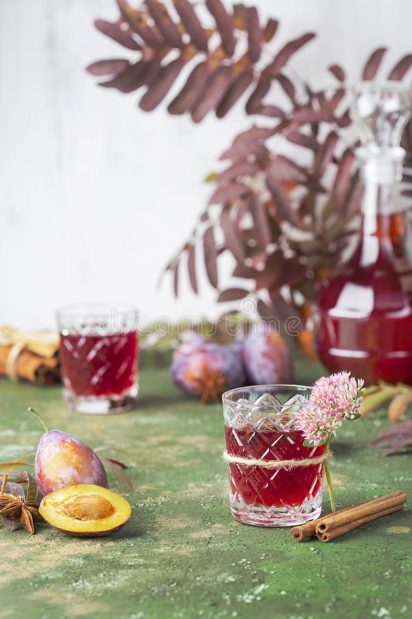 Alcoholic plum tincture. With star anise, cinnamon and cloves stock photos