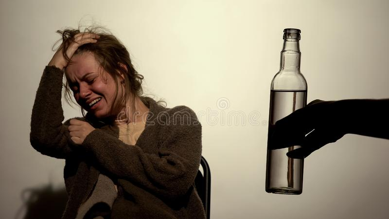Alcoholic woman suffering strong withdrawal, male hand holding bottle of vodka royalty free stock photography