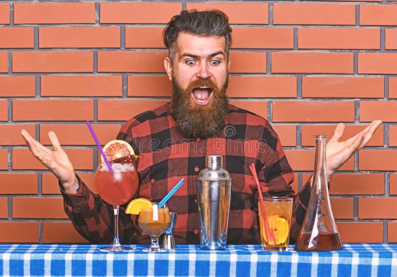 Alcoholisch drankenconcept De mens in geruit overhemd op bakstenen muurachtergrond bereidt dranken voor Barman met lange baard en royalty-vrije stock fotografie