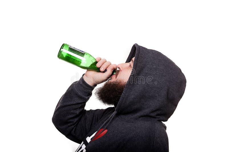 Alcoholisch met een baard en een snor in de kap Het drinken van bier F royalty-vrije stock foto