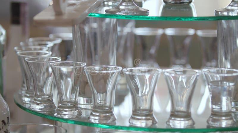 Alcoholisch Paradijs De mensen` s hand giet een alcoholische drank Voor de lijst, heel wat schotels waarin een drank giet royalty-vrije stock foto's