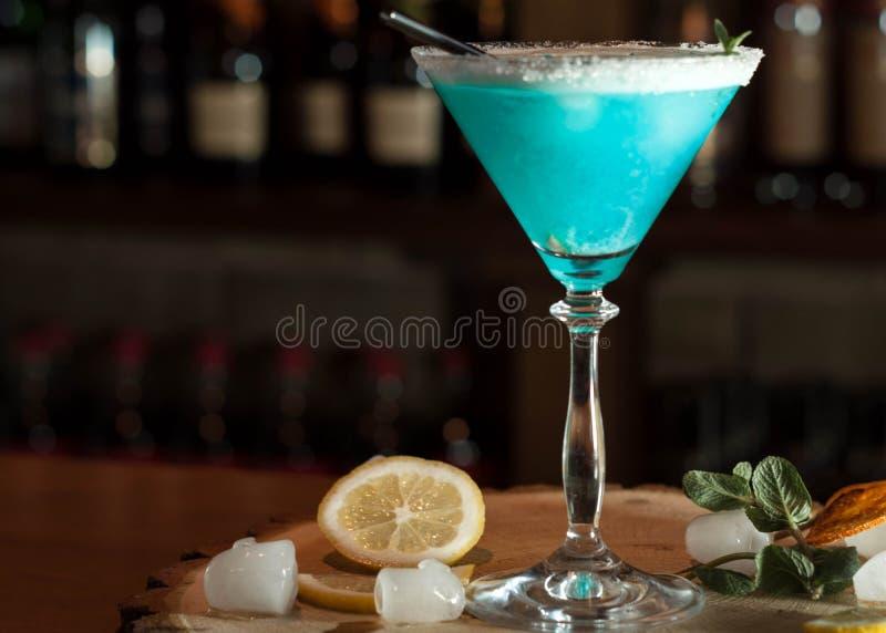 Alcoholische drank in glas met zwart het drinken stro, citroenplakken en kruiden stock afbeeldingen