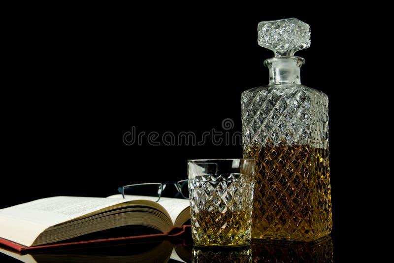 Alcoholische drank in kristalkaraf In een glas gegoten whisky op zwart glas en zwarte achtergrond Open boek met glazen royalty-vrije stock foto's