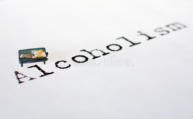 Alcoholism. A tiny model figure represents the word Alcoholism. Figure of a man is lying on a bench and has passed out drunk royalty free stock photography
