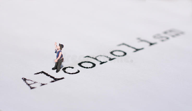 Alcoholism. A tiny model figure represents the word Alcoholism royalty free stock images