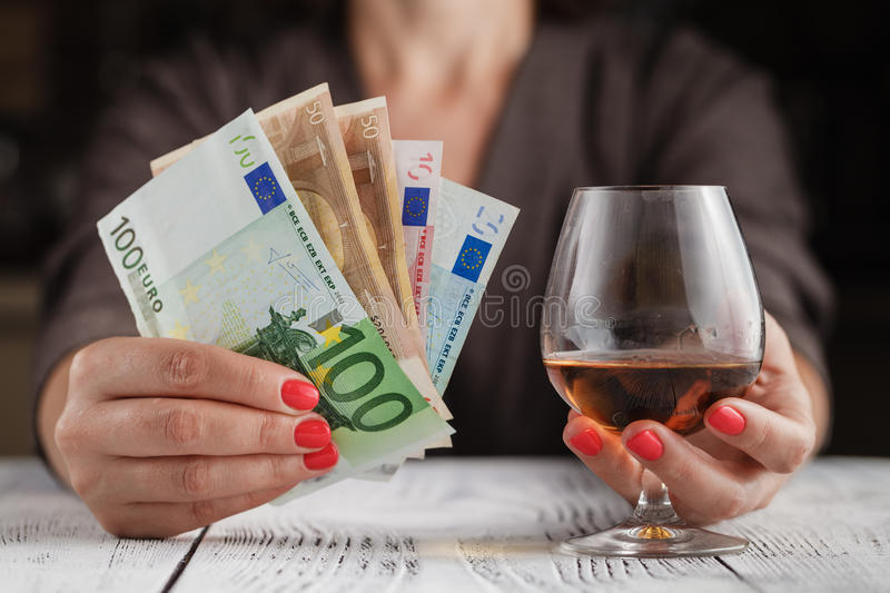 Alcoholism issue. Female take wine glass on dark toned table stock photography