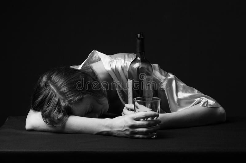 Alcoholism. Young woman is sleeping on the table. Holding a bottle and a wineglass in the hands, gray background, black and white royalty free stock image