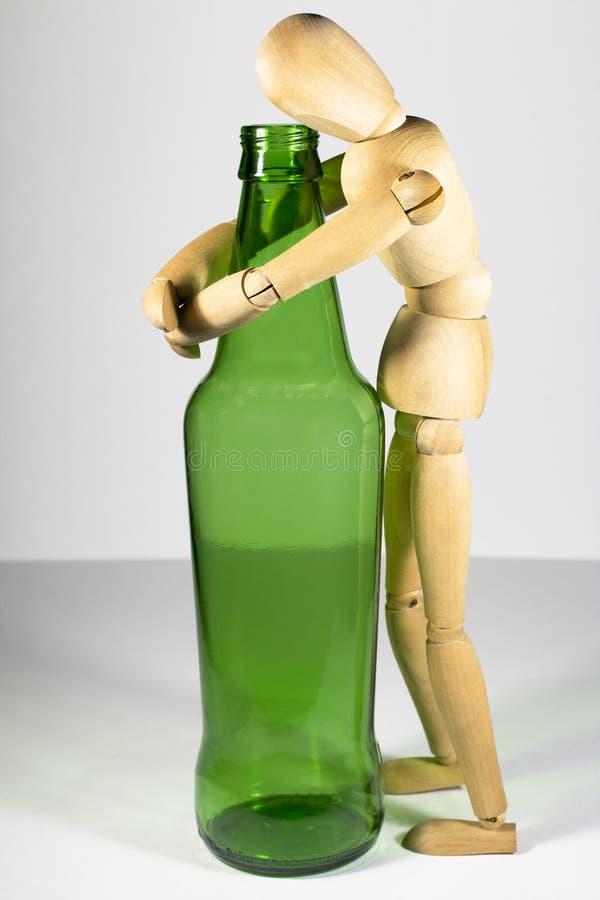 Alcoholisme, alcoholverslaving, sociaal probleem: een houten model, een eenzame alcoholist die, alcoholisch, een fles bier koeste stock foto's