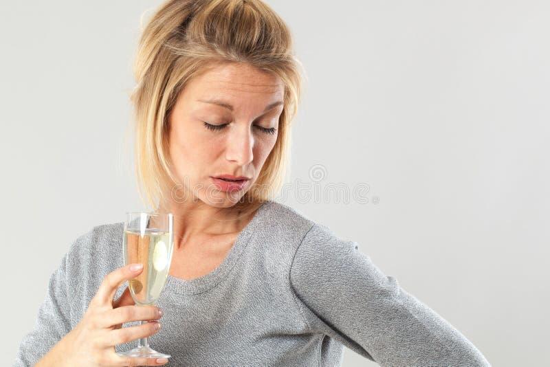 Alcoholismo femenino para la mujer rubia joven que sostiene el vino burbujeante fotos de archivo libres de regalías