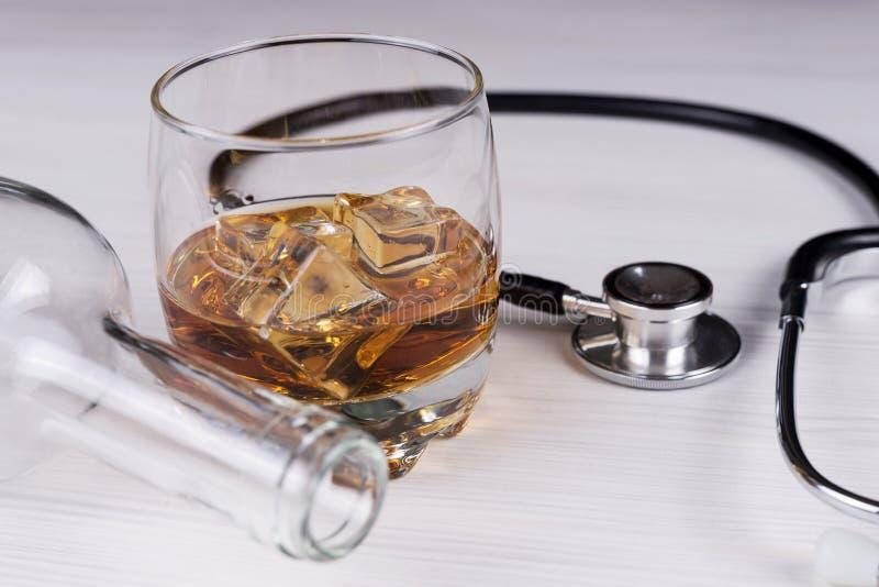alcoholisms 听诊器,玻璃用科涅克白兰地一个空的瓶 免版税库存照片