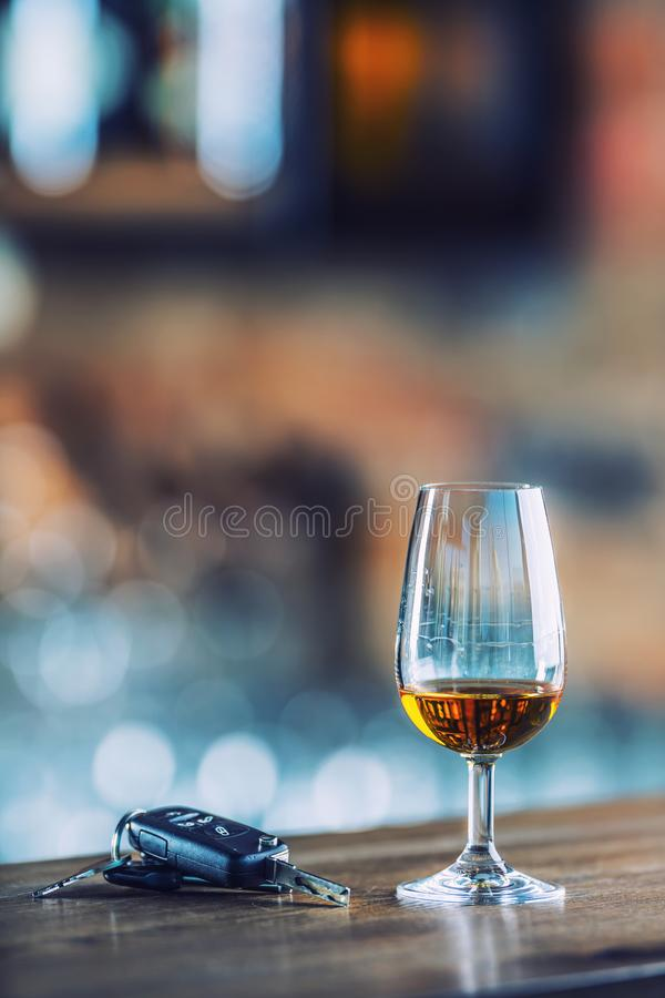 alcoholisms 杯科涅克白兰地或白兰地酒手人钥匙到的汽车 免版税库存图片