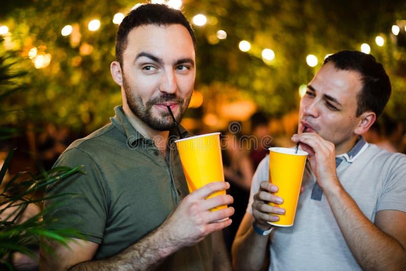Alcoholistenmensen die en pret drinken hebben bij in openlucht koffie of park Het glimlachen de vriendschapsconcept van de paaral stock afbeeldingen