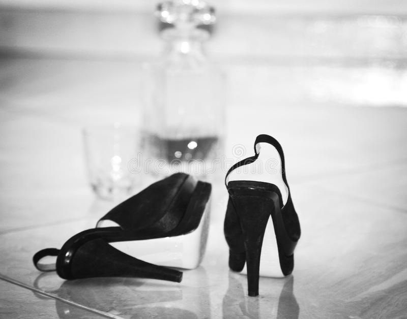 Alcohol and black woman shoes bottle liquor glass fashion accessories. Drink cognac alcohol and black woman shoes bottle liquor glass life style fashion stock image