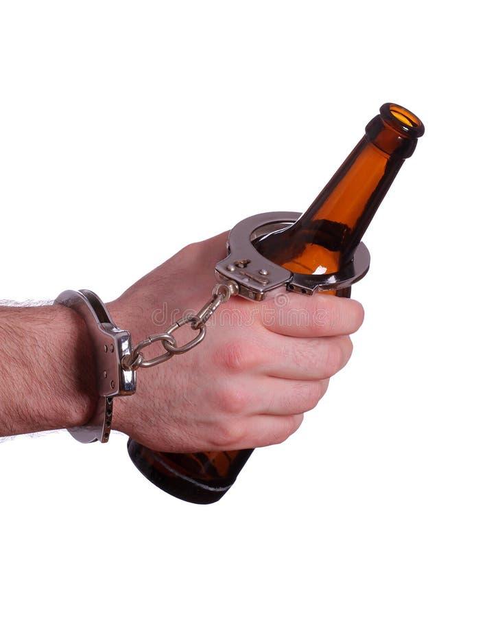Alcolismo con la manetta e la bottiglia fotografie stock libere da diritti