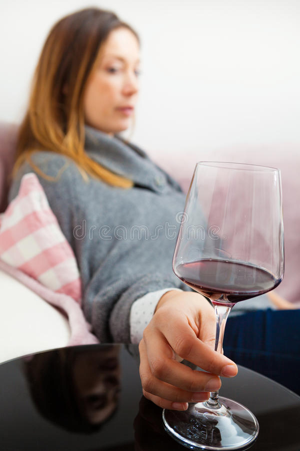 Alcolismo, donna di dipendenza di alcool Rilassandosi a casa con il vino rosso fotografia stock libera da diritti