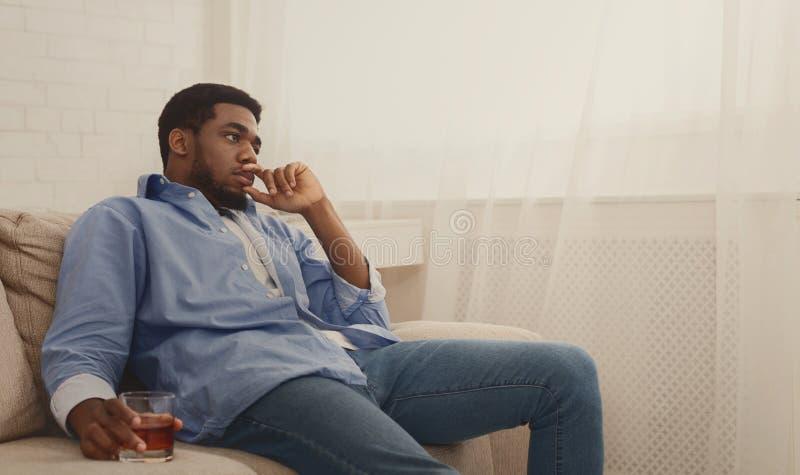 Alcool bevente del giovane uomo di colore a casa che ritiene solo fotografie stock libere da diritti