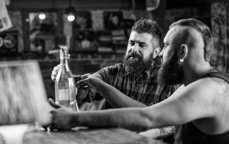 Alcool bevente dell'uomo brutale dei pantaloni a vita bassa con l'amico al contatore della barra Uomini che bevono insieme alcool fotografie stock