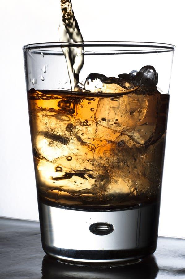 Alcool di versamento in un vetro fotografia stock libera da diritti