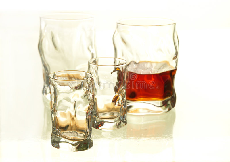 Alcool glasses. This is four glasses of alcool and one of them if half full royalty free stock photos