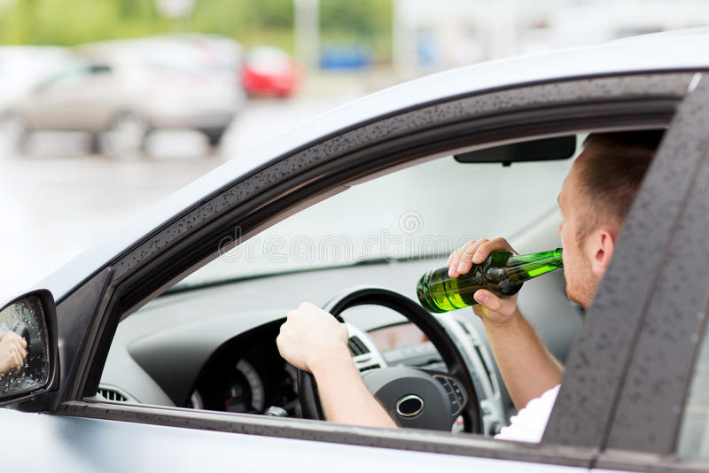 alcool potable d 39 homme tout en conduisant la voiture photo stock image du alcoolisme. Black Bedroom Furniture Sets. Home Design Ideas