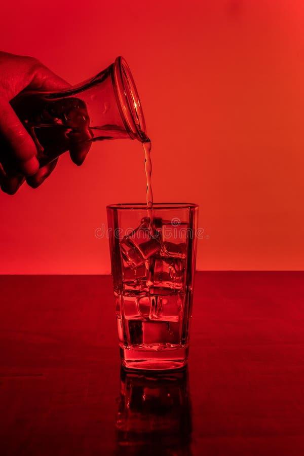 Alcool se renversant dans plein en verre de la glace avec images stock