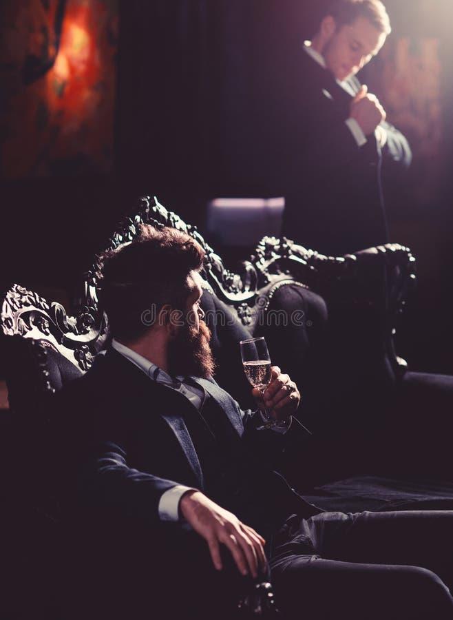 Alcool, stile di vita ricco, affare, concetto dei soldi Il capo in vestito di lusso si siede sul sofà d'annata Uomo maturo con la fotografie stock