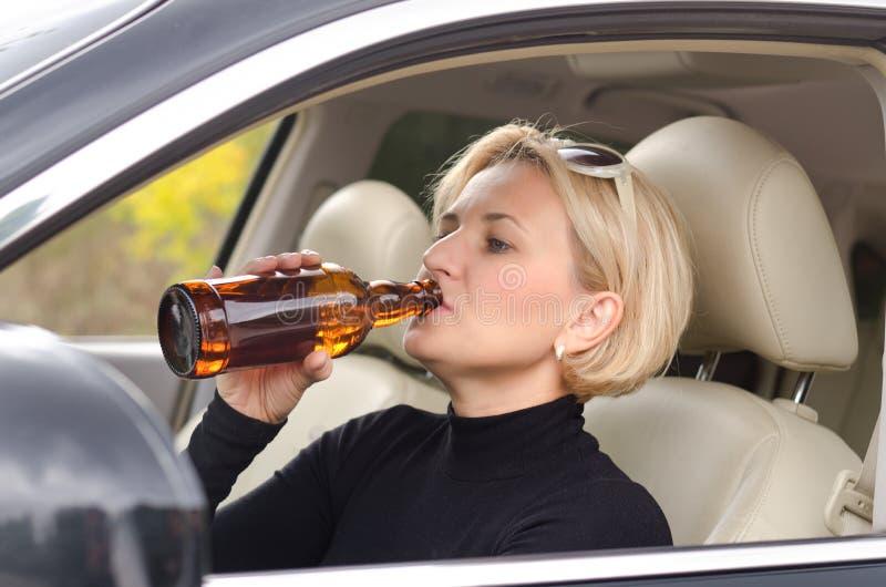 Alcoolique de femme buvant comme elle conduit la voiture photo libre de droits