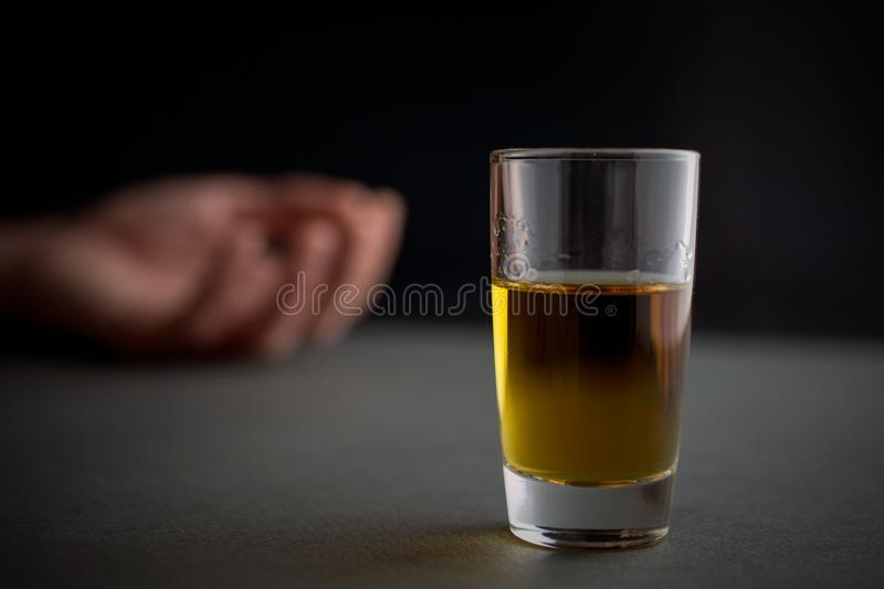 Alcoolismo e vidro do abuso de álcool da bebida do uísque ou do conhaque ou do álcool foto de stock