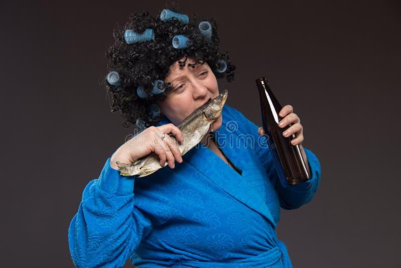 Alcoolismo fêmea A mulher gorda pobre só envelheceu a cerveja bebendo e foto de stock