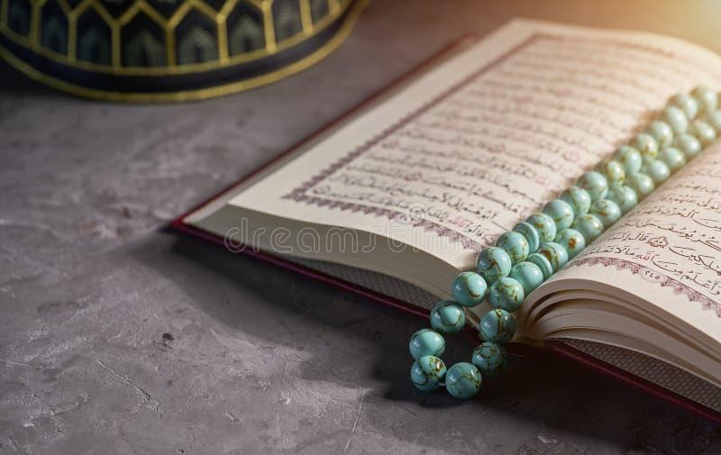 Alcorão islâmico do livro com grânulos do rosário e para rezar o chapéu para muçulmanos no fundo cinzento fotos de stock