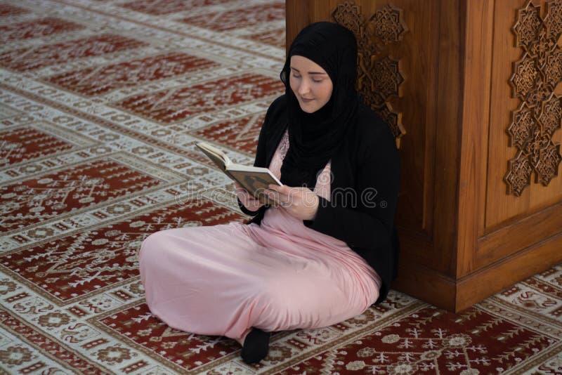 Alcorão muçulmano novo da leitura da mulher fotos de stock royalty free