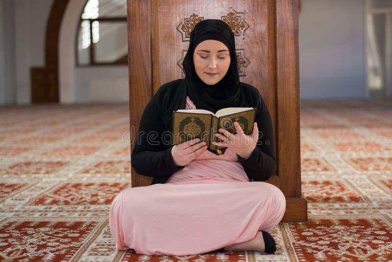 Alcorão muçulmano novo da leitura da mulher fotografia de stock royalty free