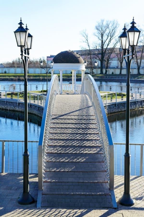 Alcova branca bonita no parque Vista da ponte que conduz à alcova no lago imagem de stock royalty free