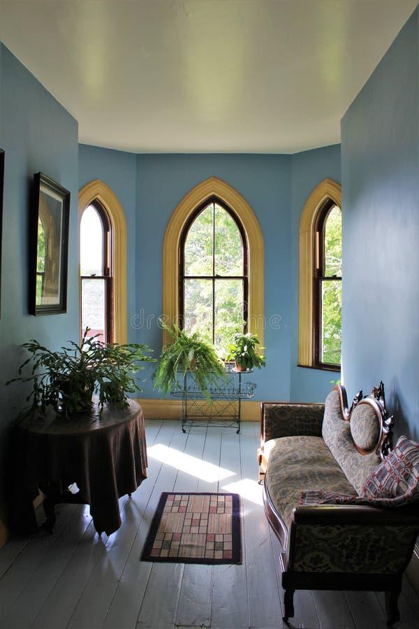 Alcova romântica no último andar de uma mansão com uma tabela e um sofá e umas plantas que negligenciam a vila histórica de Sherb imagens de stock royalty free