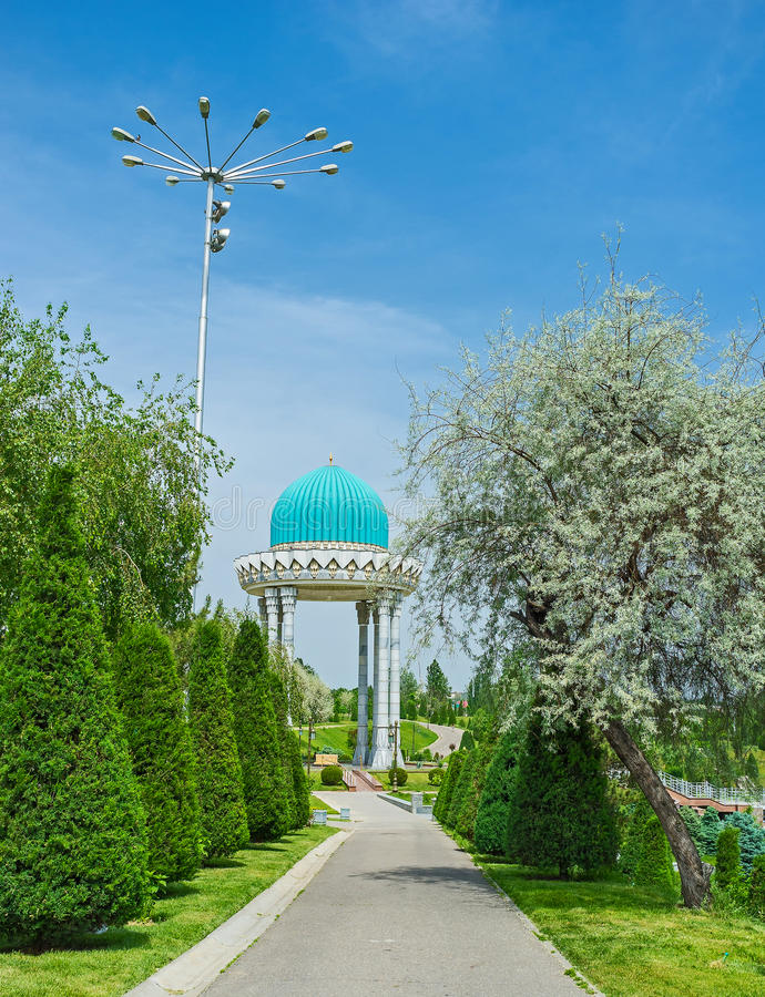 The alcove with blue dome. The scenic memorial alcove in asian style among the greenery of large garden, Tashkent, Uzbekistan stock photo