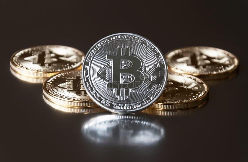 Alcun il bitcoin delle monete d'argento e dell'oro si trova o resta sul bordo su un fondo scuro Il concetto di valuta cripto fotografie stock