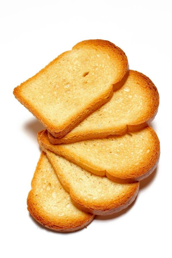 Alcune fette di pane tostato su priorità bassa bianca fotografia stock