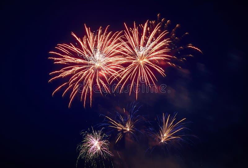 Alcune scariche dei fuochi d'artificio festivi nel cielo notturno, rosso-gialle fotografia stock libera da diritti