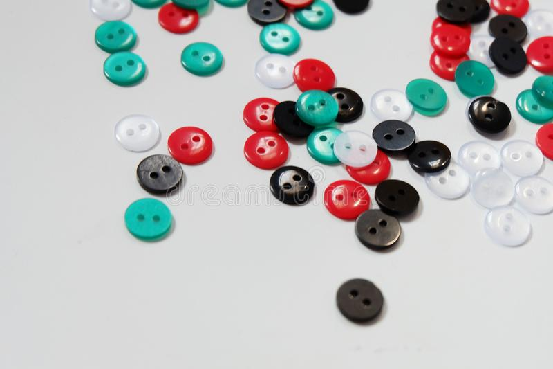 Alcuni dei bottoni di cucito disposti a fondo bianco fotografie stock
