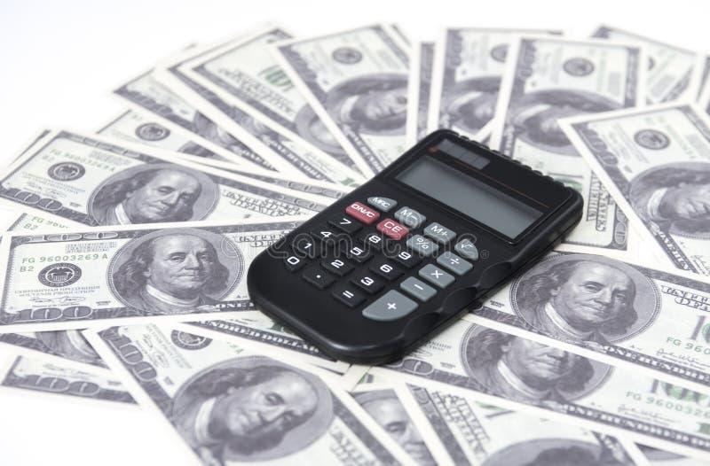 Alcuni dollari e un calcolatore sulla tavola, sulla finanza e sul risparmio Concetto di affari fotografie stock libere da diritti