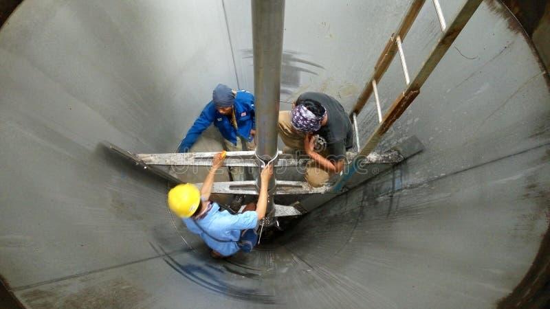 Alcuni lavoratori stanno lavorando in carri armati sui progetti di costruzione fotografia stock