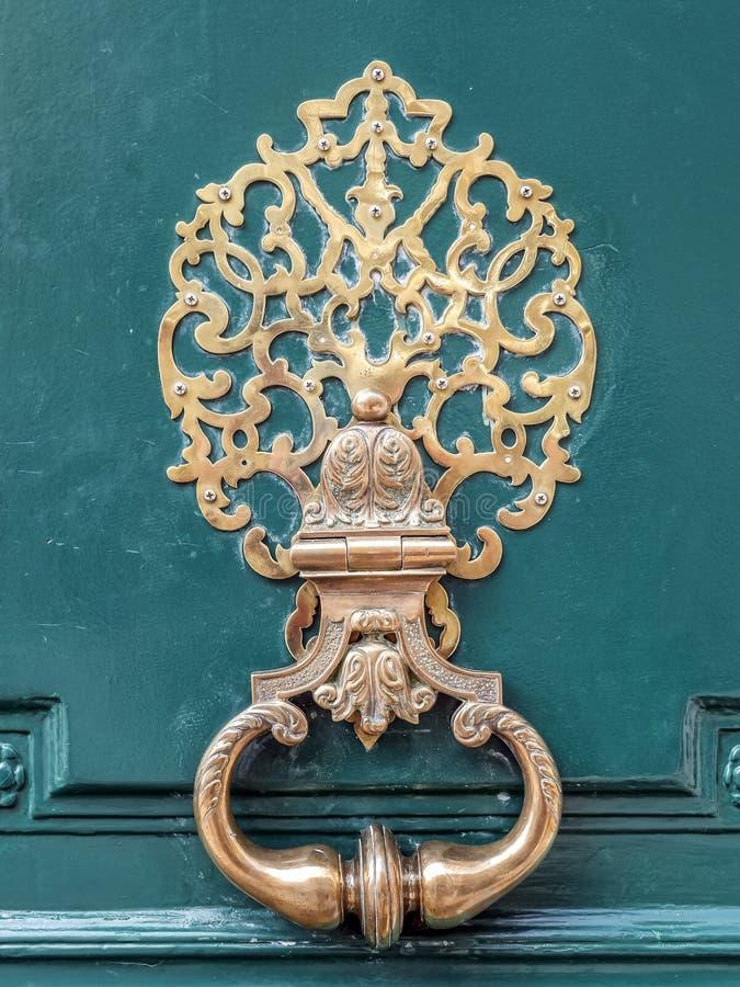 Aldaba de cobre amarillo elegante en puerta de madera verde fotografía de archivo