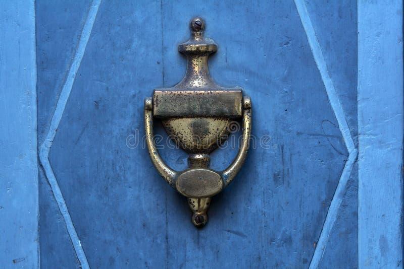 Aldaba vieja del latón en una puerta azul imagen de archivo libre de regalías